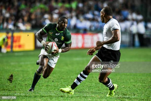 Siviwe Soyizwapi of South Africa runs with the ball as Osea Kolinisau of Fiji looks to tackle him during the Cup Final on the third day of the Hong...