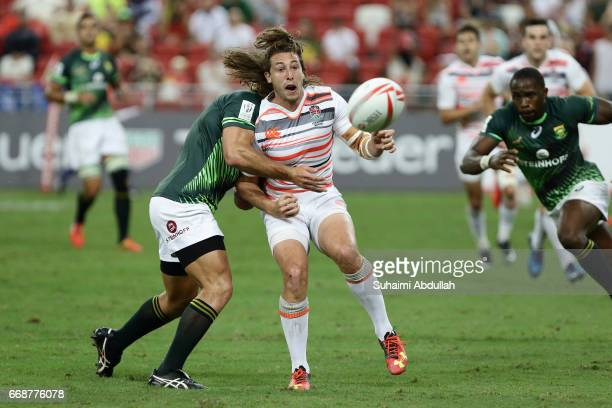 Siviwe Soyizwapi of South Africa tackles Dan Bibby of England during the 2017 Singapore Sevens match between South Africa and England at National...