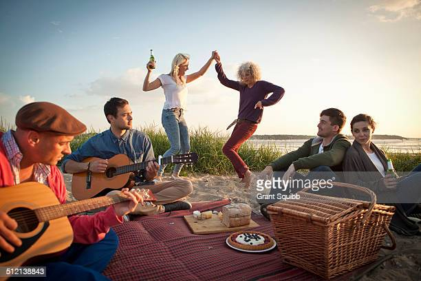 Six adult friends partying and dancing on Bournemouth beach, Dorset, UK