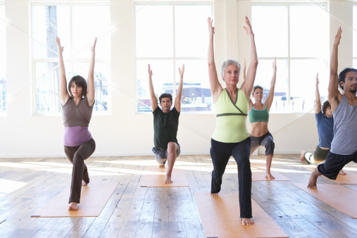Six adults practicing yoga, arms raised - gettyimageskorea