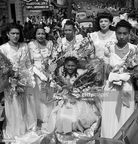 Six AfricanAmerican Mardi Gras princesses ride a parade float in their formals New Orleans Louisiana circa 1950