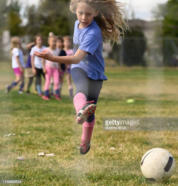 Six and seven-year old players on the girls Rainbow Unicorn team work on shooting drills during a practice in Los Angeles, California on April 30,...