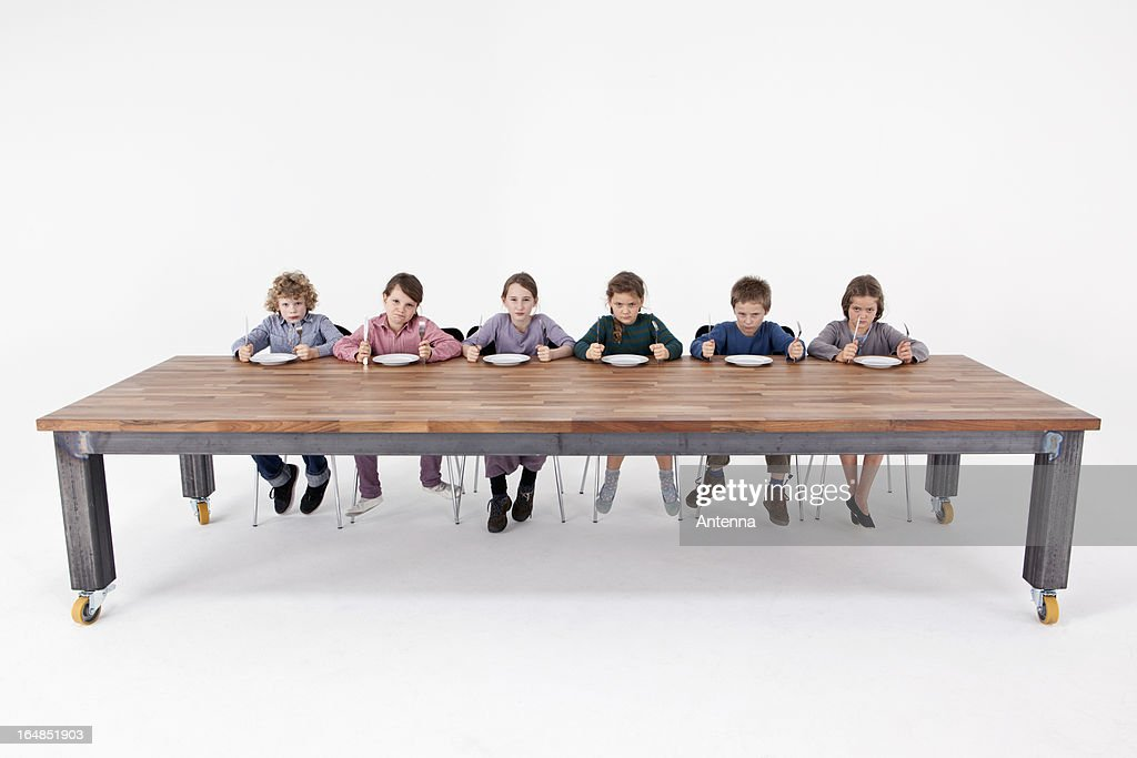 Six angry kids holding knives and forks impatiently waiting for food : ストックフォト
