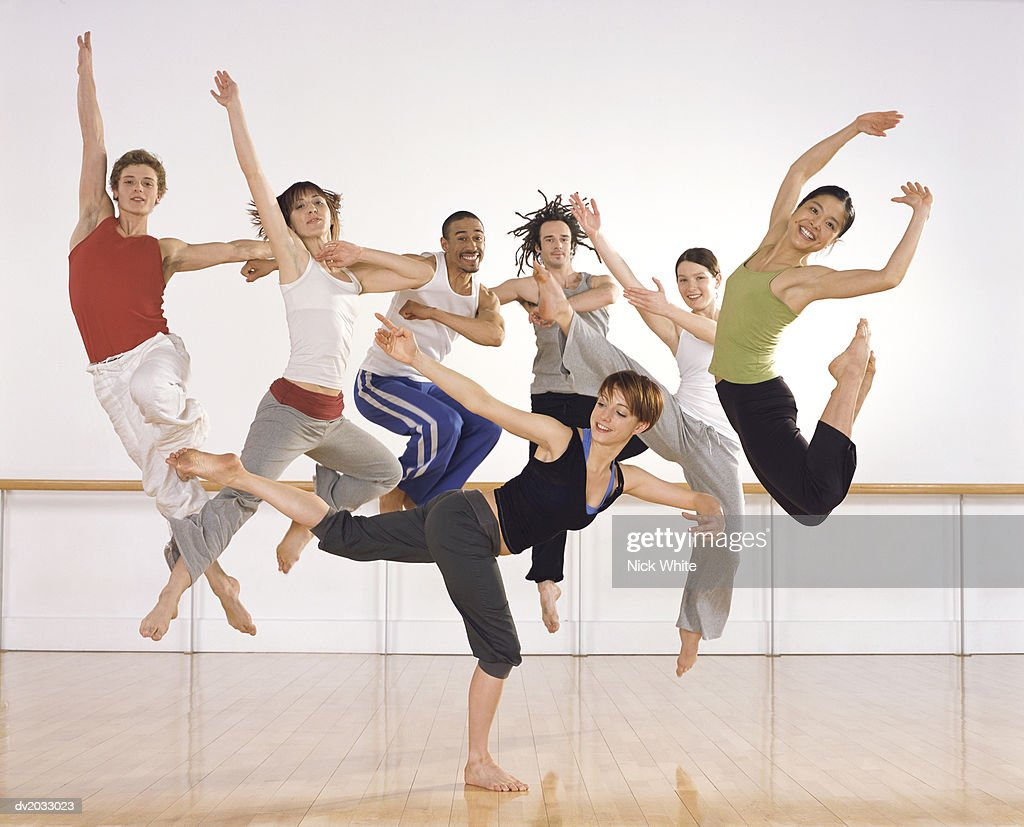 Six ballet Dancers Jumping in Mid Air, One Female Ballerina Standing on One Leg in Front of Them : Stock Photo