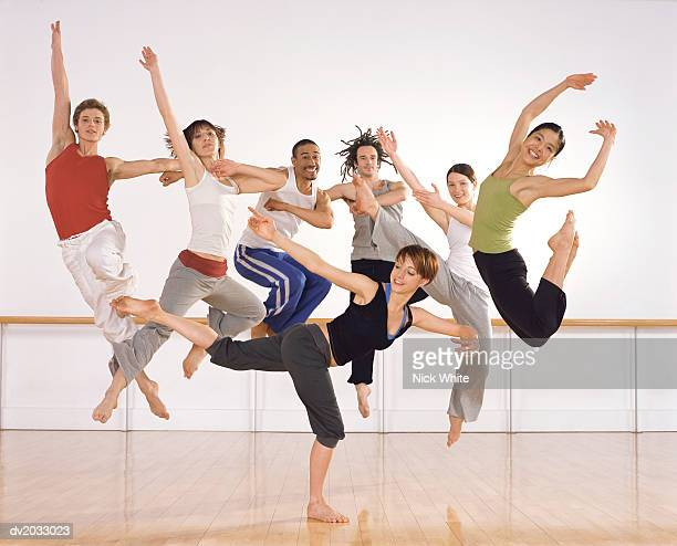 Six ballet Dancers Jumping in Mid Air, One Female Ballerina Standing on One Leg in Front of Them