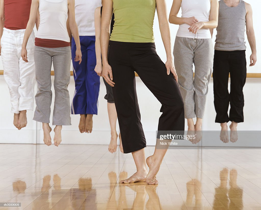 Six Ballet Dancers Jumping in Mid Air, One Standing in Front of Them : Stock Photo