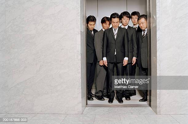 Six businessmen in open elevator looking downwards