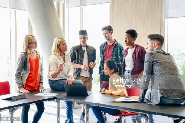 six college students listening to mature female lecturer with laptop in classroom - classroom stock photos and pictures