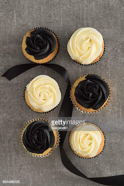 Six cup cakes with black and cream coloured buttercream topping and black ribbon