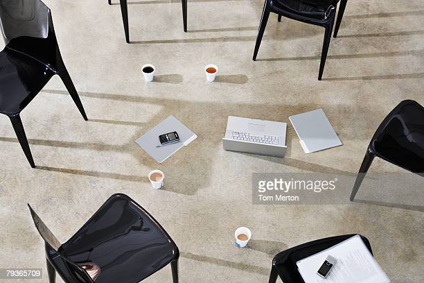 Six empty chairs indoors around a laptop and folders