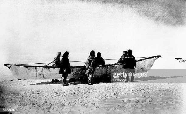Six Eskimos standing beside native skinboat or umiak on sled Point Barrow Alaska 1935