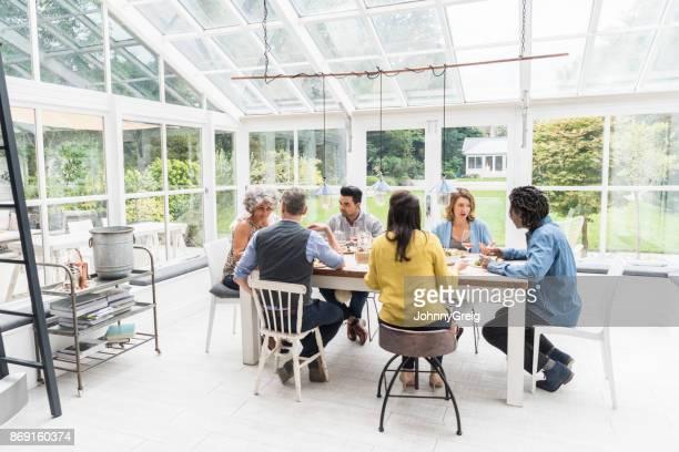 Seis amigos sentados alrededor de la mesa de la cena en naturalmente iluminado hablando del Conservatorio