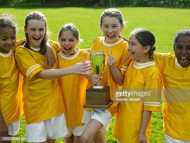 six girls (9-11) in soccer uniforms holding trophy, laughing - only girls stock pictures, royalty-free photos & images