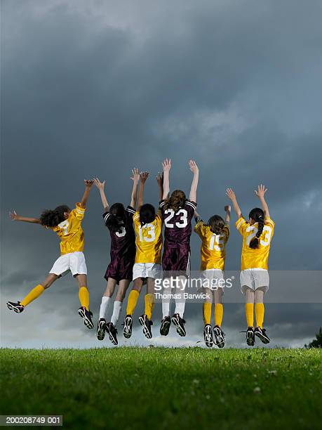 six girls (9-11) jumping on soccer field, arms raised, rear view - only girls stock pictures, royalty-free photos & images