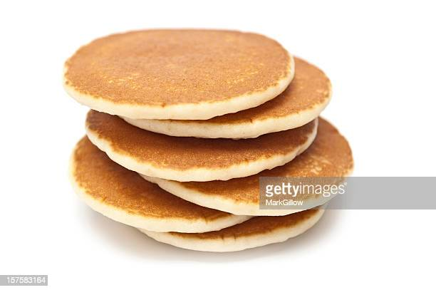 Six golden brown pancakes stacked in uneven arrangement