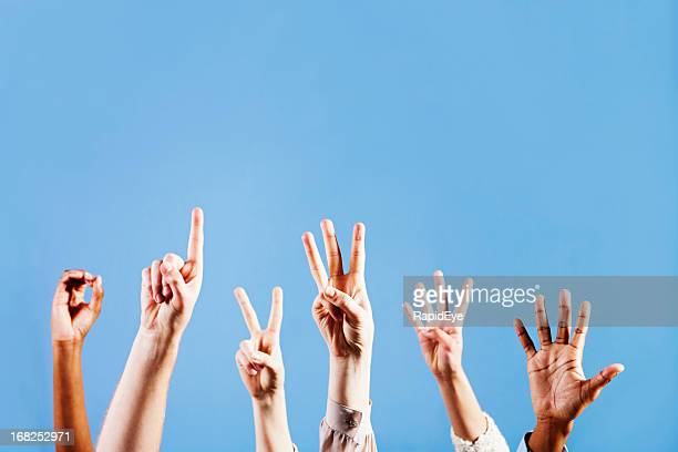 Six hands count from 0 to 5 against blue background