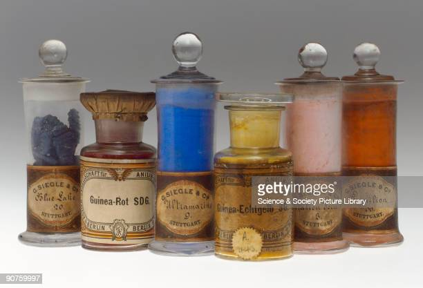 Six jars containing synthetic colorants Blue Lilac 20 manufactured by G Siegle Co of Stuttgart GuineaRot SDG by Actien Gesellschaft für Anilin...