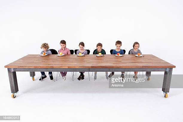 Six kids looking down at apples on their plates with uncertainty