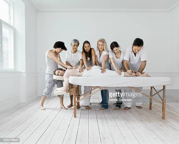 Six masseurs massaging a male patient