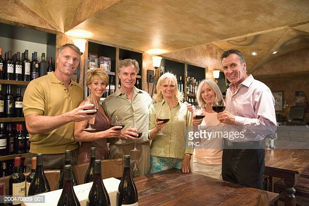 six mature adults drinking red wine in wine cellar, portrait - medium group of people stock pictures, royalty-free photos & images