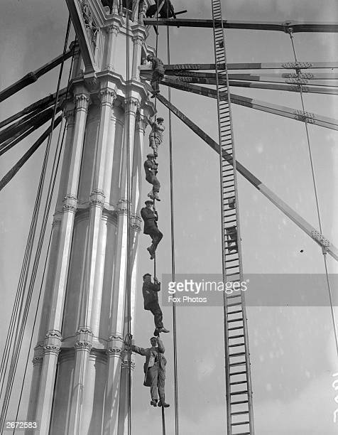 Six men climbing up a rope beside one of the pillars of the Albert Bridge London on which they are working
