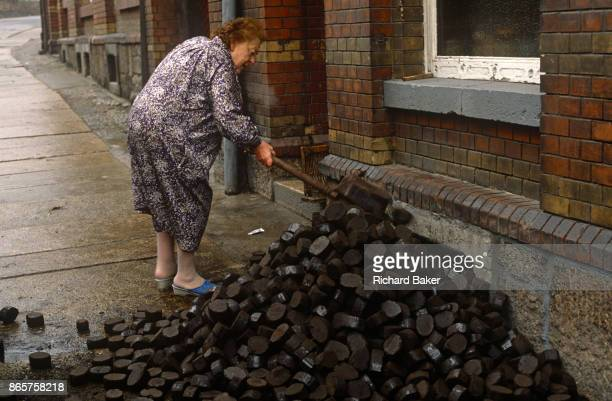 Six months after the fall of the Berlin Wall a lady shovels East German Lignite coal briketts left outside her home on 1st June 1990 in Aue Saxony...