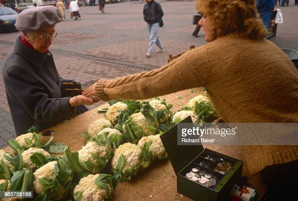 Six months after the fall of the Berlin Wall an elderly lady is handed her change after buying some cauliflowers at a market stall on 1st June 1990...