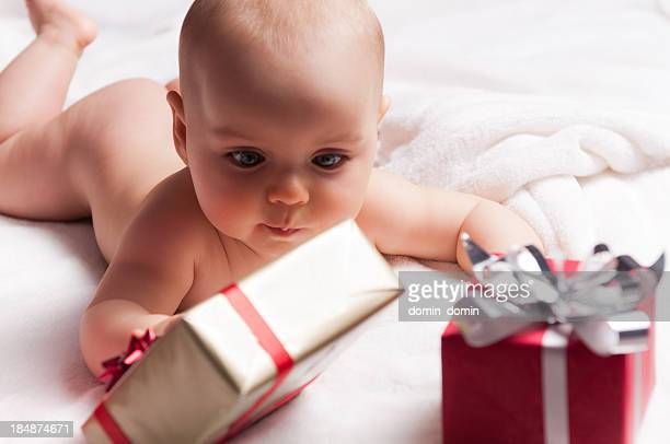 Six mois beau nu bébé jouant avec cadeaux