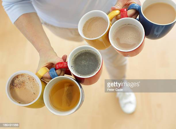 Six mugs with hot drinks being carried