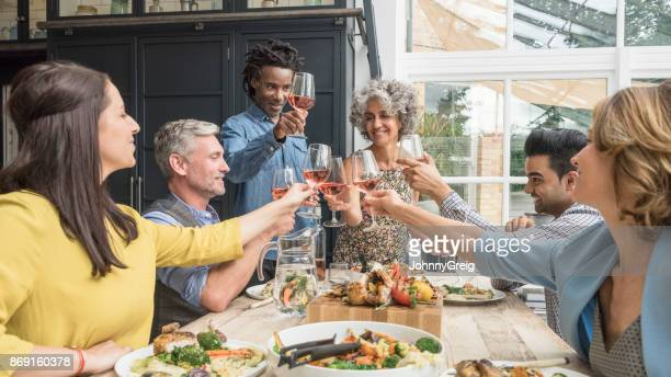 Six multi racial friend toasting wine glasses at dinner party
