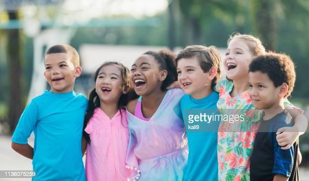 sechs multiethnische kinder im schwimmbad - person gemischter abstammung stock-fotos und bilder