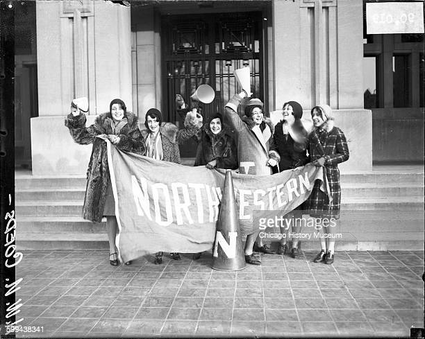Six Northwestern University coeds holding a Northwestern banner and megaphones, standing in front of a campus building, Evanston, Illinois, 1929.