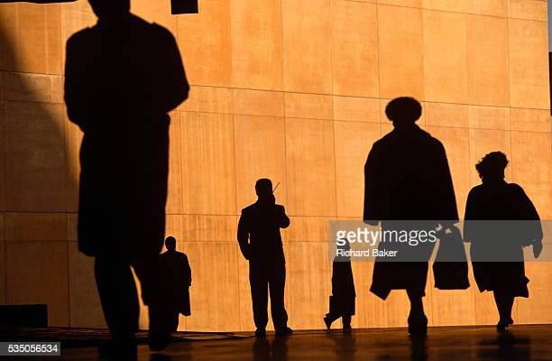 Six office workers are silhouetted against the large orange wall of the Credit Lyonnais Bank as they rush to work in Broadgate London