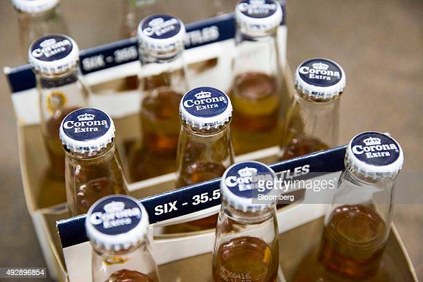 Six packs of bottled Corona beer produced by AnheuserBusch InBev NV sit on display in a store in Paris France on Thursday Oct 15 2015 AB Inbev is...