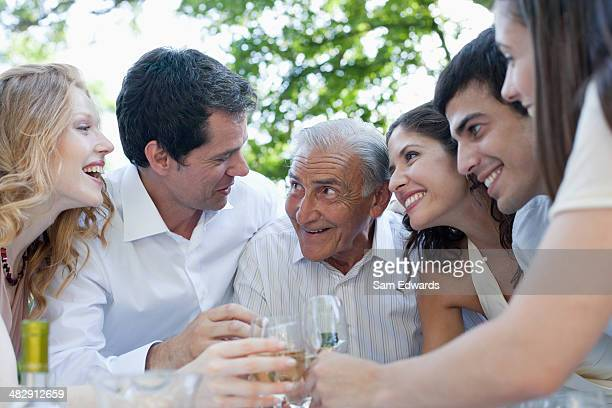 six people outdoors toasting champagne and smiling - generation gap stock pictures, royalty-free photos & images