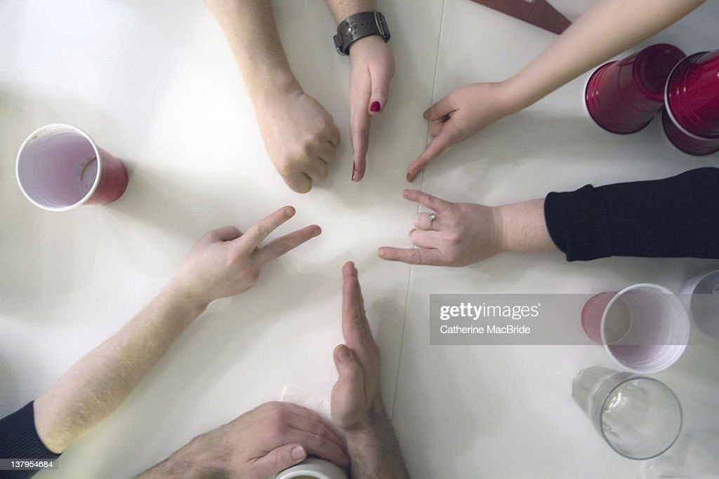 Six people playing rock, paper scissors at party : Stock Photo
