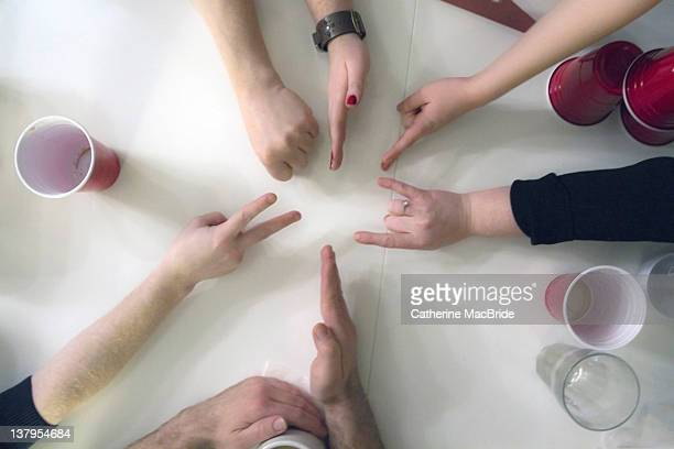 six people playing rock, paper scissors at party - catherine macbride stock pictures, royalty-free photos & images