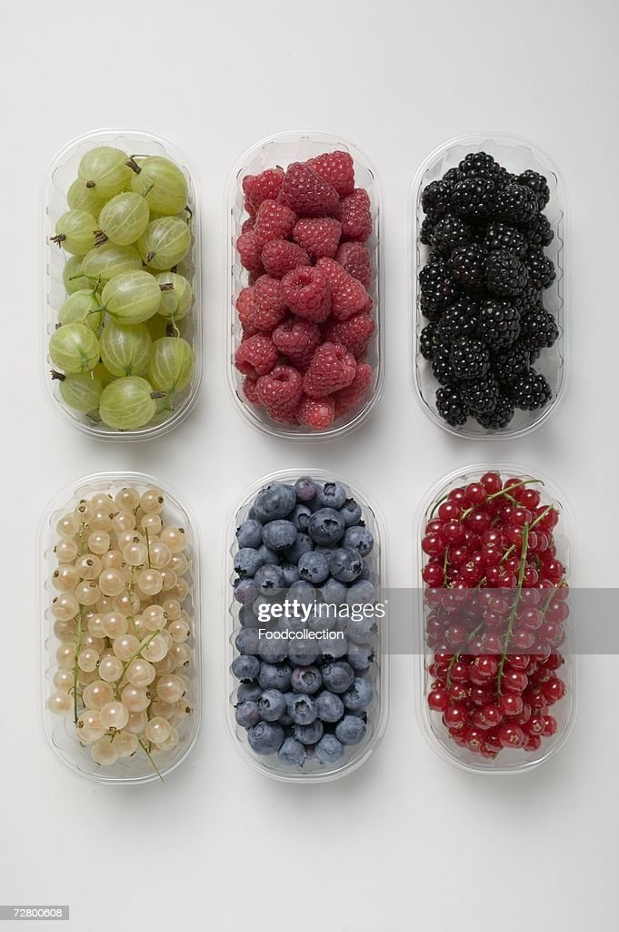 Six plastic punnets of different berries : Stock Photo