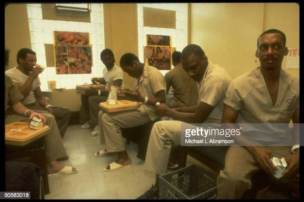 Six prisoners sitting on bunks in dormitorystyle room in Cook County Jail