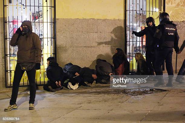 Six protestors are arrested and handcuffed by undercover police helped by police in riot gear during a protest against the 'Clamp law' in Madrid...