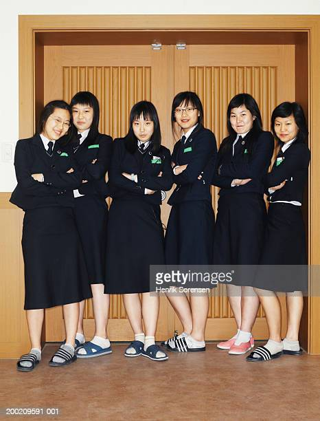 Six schoolgirls (14-16) standing by doorway, arms folded, smiling