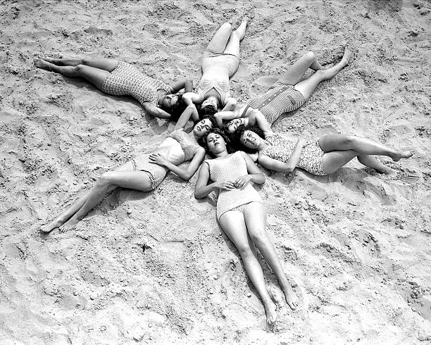 Six shapely lasses hit the beach with a view to soaking up s