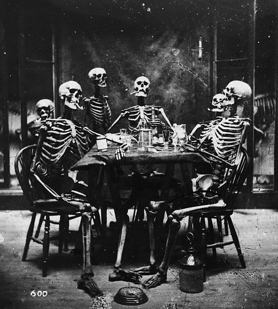 Six skeletons smoking around the dinner table, circa...