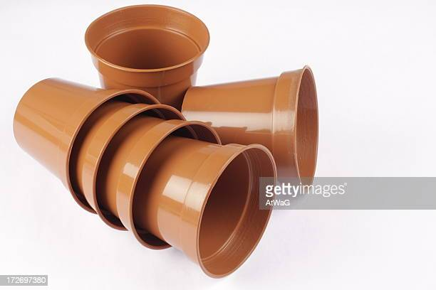 Six small empty brown plastic plant pots on white background