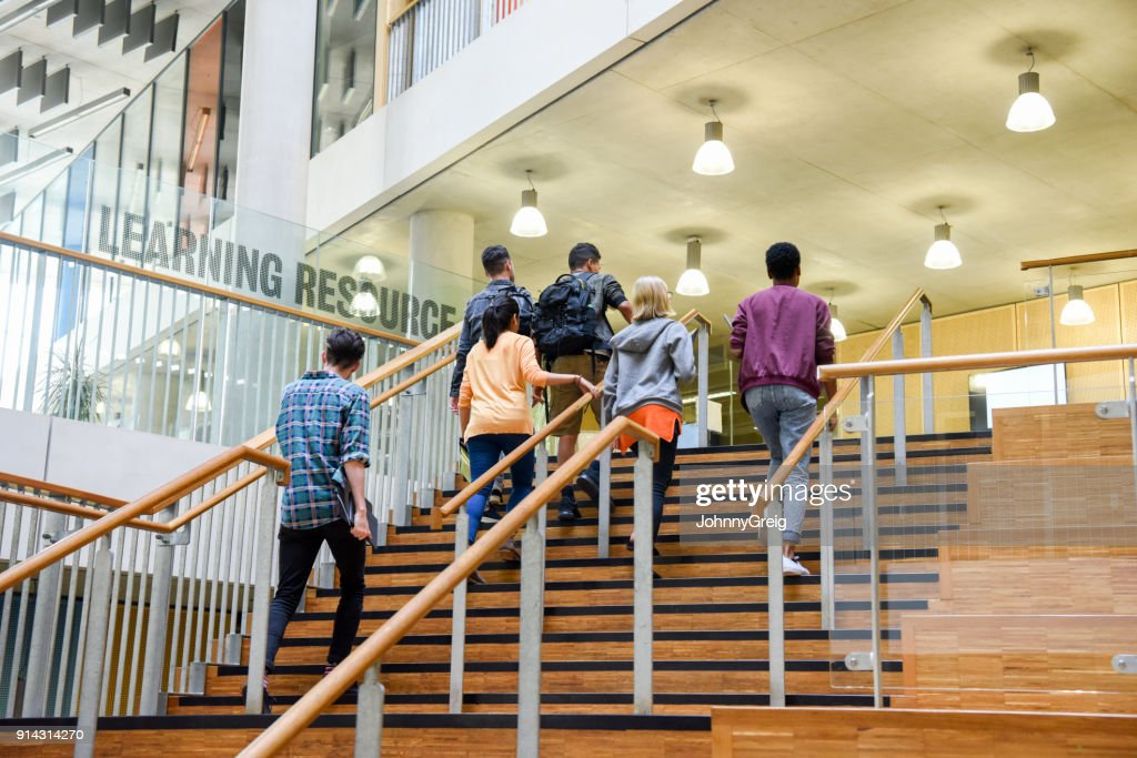 Six students walking up wooden steps in modern college building : Stock Photo