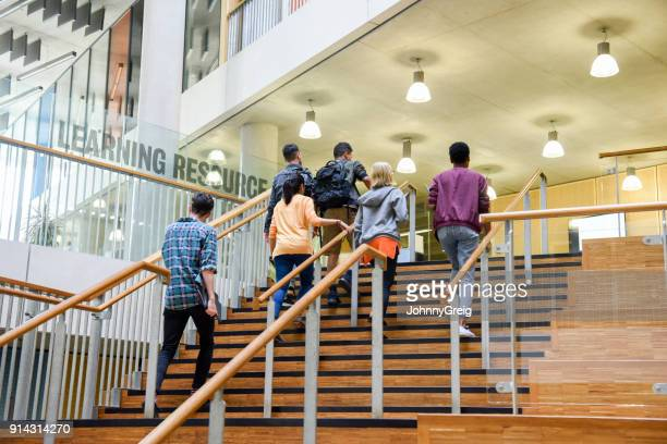 Six students walking up wooden steps in modern college building