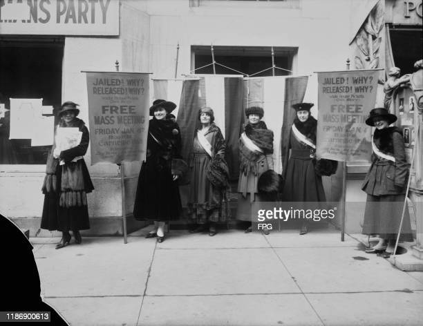 Six suffragettes holding banners that read: 'Jailed! Why? Released! Why? White House Pickets Own Story; Free Mass Meeting, Friday January 4th, 8:30...