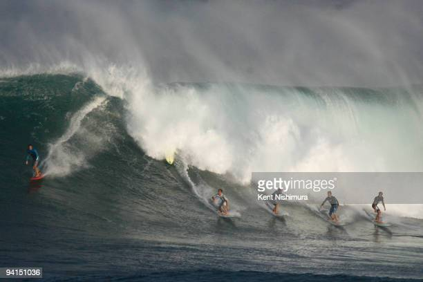 Six surfers drop into a wave during precontest surfing at the Eddie Aikau BigWave Invitational on December 8 2009 in Waimea Hawaii The rare contest...