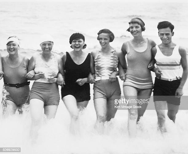 Six swimsuited adults link arms and wade through the surf on a beach in Germany