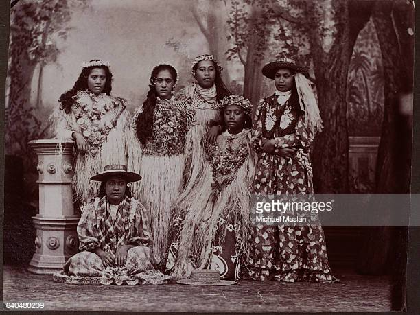 Six Tahitian women pose in front of a painted backdrop Four wear long dresses made of grass and flowers and headbands made of flowers The other two...